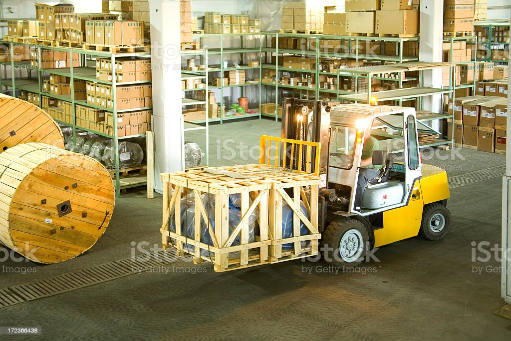 Yellow forklift inside of a warehouse in motion royalty-free stock photo