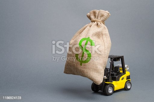istock Yellow forklift truck carries a big bag of money. Attracting investment in the development and modernization of production and business, infrastructure projects. Revenue, profit, sales and liquidity. 1156524123