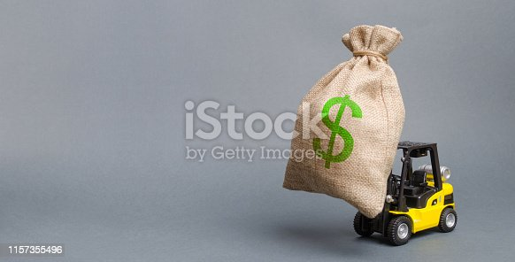 istock Yellow forklift truck carries a big bag of money. Attracting investment in the development and modernization of production and business projects. Revenue, profit, sales. Banner, copy space 1157355496