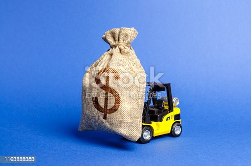istock Yellow forklift truck carries a big bag of money. Attracting investment in the development and modernization of production and business projects. Revenue, profit, sales. super profit. copy space 1163888353
