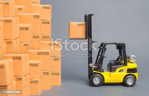 1155852718istockphoto Yellow Forklift truck picks up a box on a pile of boxes. Service storage of goods in a warehouse, delivery and transportation. Freight shipping, delivery. Import and export, commodity exchange 1158582060
