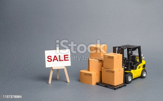 1155852718istockphoto Yellow Forklift truck with cardboard boxes and stand with the word sale. sale of goods, big discounts on goods of the outgoing season. commodity exchange with other countries. Attracting buyers 1157378964