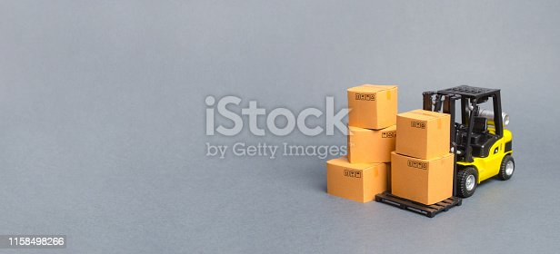1155852718istockphoto Yellow Forklift truck with cardboard boxes. Service storage of goods in a warehouse, delivery and transportation. Freight shipping, delivery. Import and export, commodity exchange. Banner, copy space 1158498266