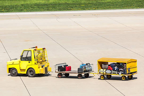 Yellow freight trolleys with loaded baggage stock photo