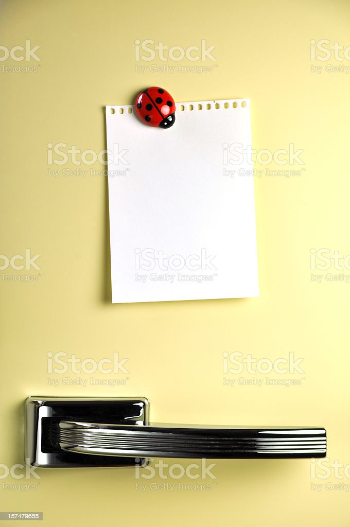 A yellow fridge with a white paper held by ladybug magnet royalty-free stock photo
