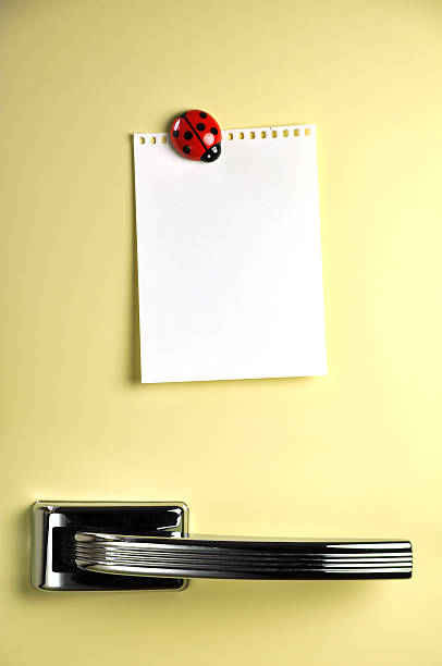 A yellow fridge with a white paper held by ladybug magnet stock photo