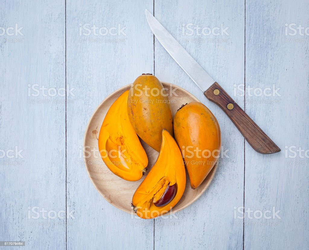 Yellow fruit on wooden plate stock photo