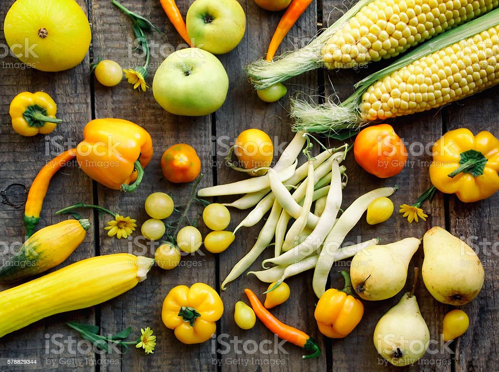 yellow fruits and vegetables on a wooden background stock photo