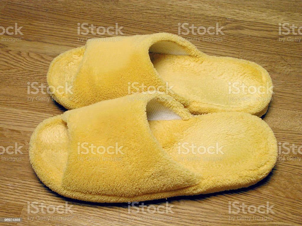 yellow furry plush slippers on wooden floor royalty-free stock photo