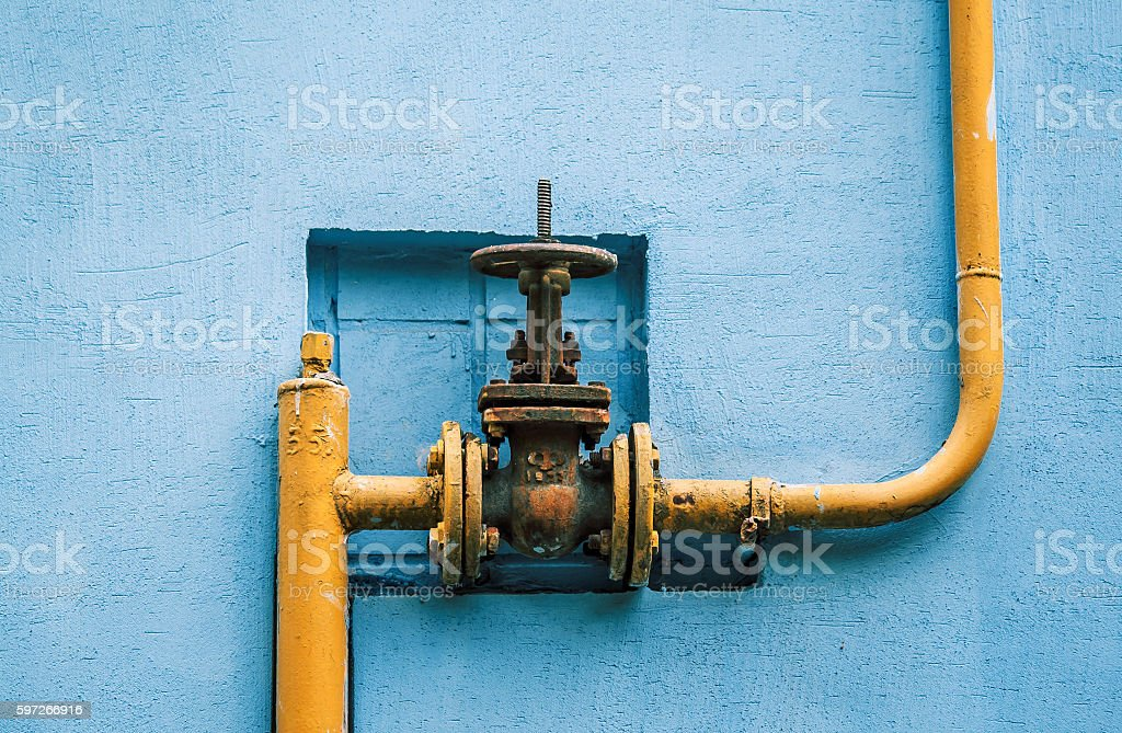 yellow gas pipe with a valve on the blue wall Lizenzfreies stock-foto