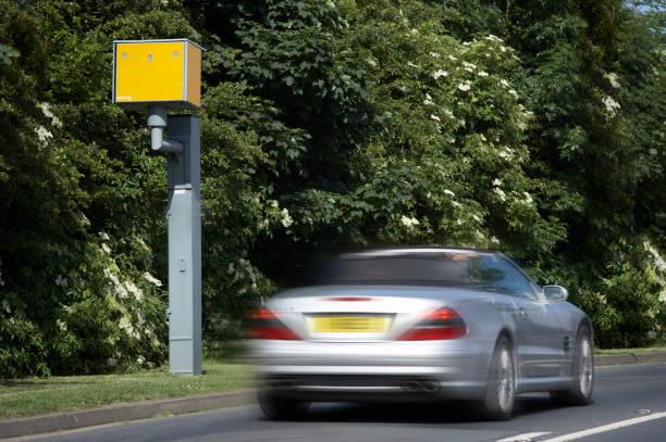 gatso blitzer mit auto beschleunigt vorbei in west yorkshire gelb - geschwindigkeitskontrolle stock-fotos und bilder