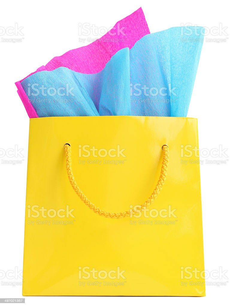 Yellow gift bag stuffed with pink and turquoise tissue paper stock photo