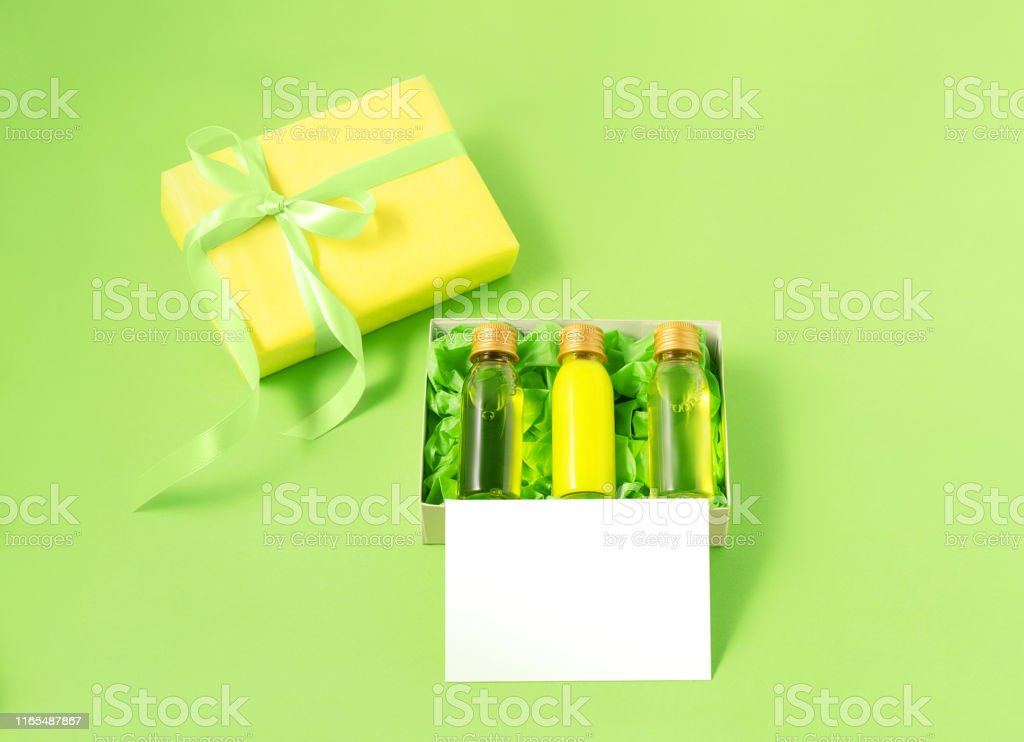 Yellow gift box with three small mockup bottles of spa cosmetic...