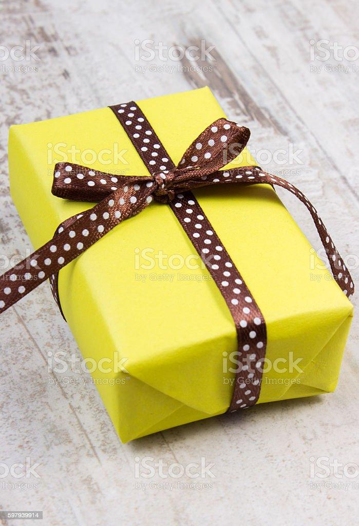 Amarelo presente de natal ou festa na prancha de madeira foto royalty-free