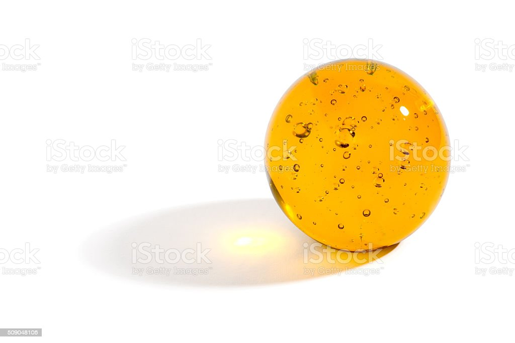 Yellow glass sphere casting a shadow stock photo