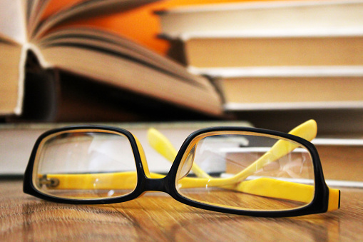Yellow glasses and old books so close