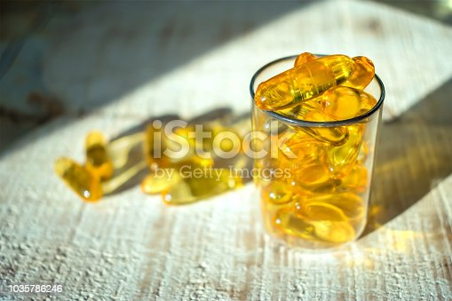 istock Yellow gold oil vitamin, omega 3 capsules in a glass beaker in the rays of light on a wooden background. Close up, selective focus 1035786246