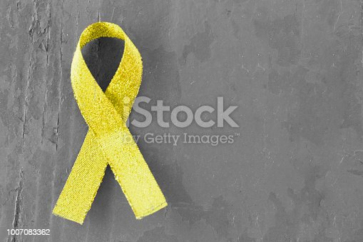 istock yellow, gold ribbon on black and white wooden background, close-up, copy space, medical concept, Suicide Prevention Day 1007083362