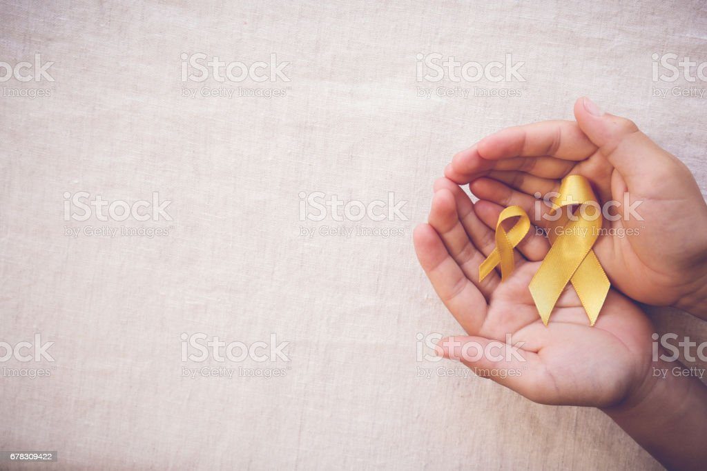 yellow gold ribbons on hands, Sarcoma Awareness, Bone cancer, Liver cancer, Bladder Cancer, childhood cancer awareness stock photo