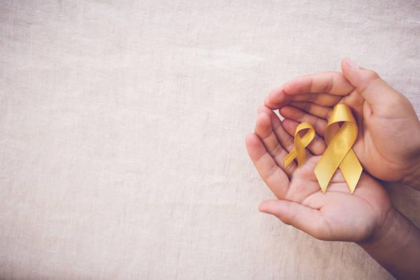 yellow gold ribbons on hands, Sarcoma Awareness, Bone cancer, Liver cancer, Bladder Cancer, childhood cancer awareness - foto de acervo