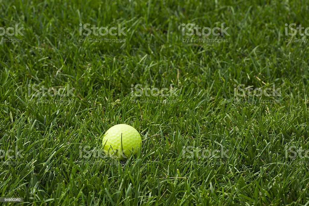 yellow golf ball in the grass royalty-free stock photo