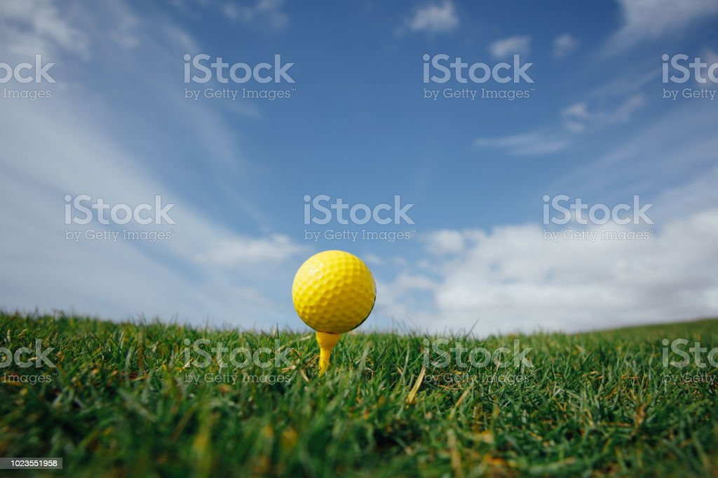 yellow golf ball on tee, green grass and blue sky background,...
