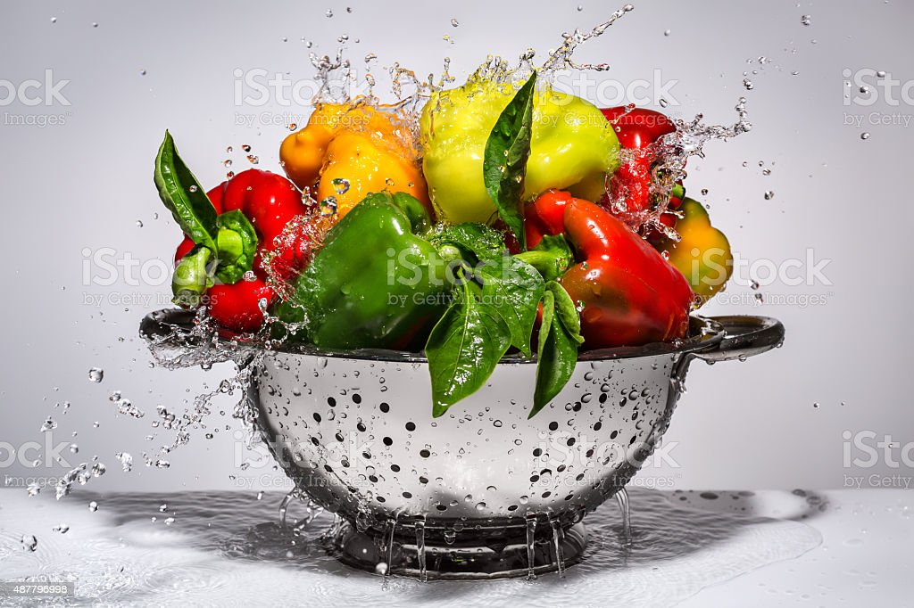 Yellow, green and red peppers in a colander stock photo