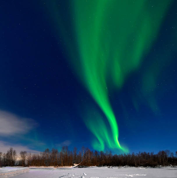 Yellow green Northern lights (Aurora borealis) over wooden shed in snowy landscape of Finland stock photo