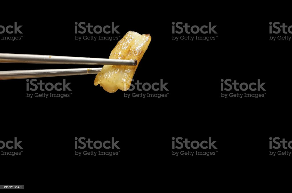 yellow grilled pork fat between silver chopsticks on black background stock photo