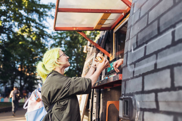yellow hair woman receives vegan burger from food truck - living a sustainable lifestyle foto e immagini stock