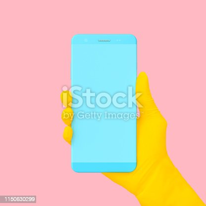 istock Yellow hand holding phone blue color on pink background. 1150630299