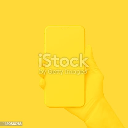 istock Yellow hand holding phone on yellow background. 1150630263