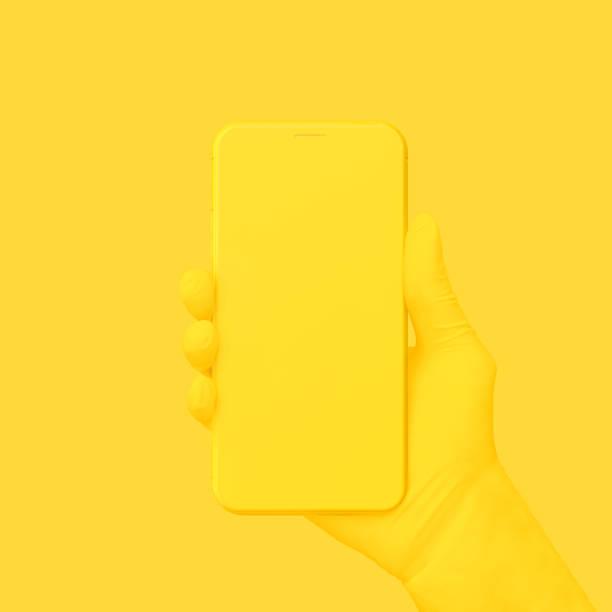 yellow hand holding phone on yellow background. - fumetto creazione artistica foto e immagini stock