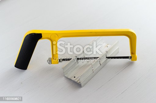 istock yellow hand saw and aluminium miter box for hobby in home workshop 1165569821