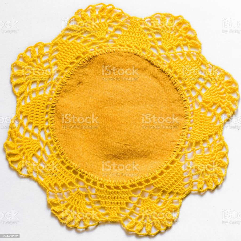 Yellow handmade lace tablecloth texture on white background stock photo