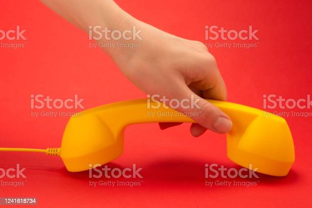 Yellow handset on a red background in woman hand picture id1241618734?b=1&k=6&m=1241618734&s=612x612&h=j2job0iyixlqnptwnnup gm5lw2fwecgvk 62anfeji=