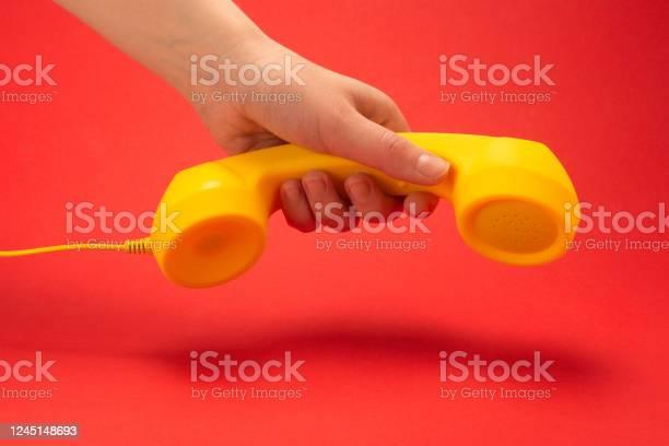 Yellow handset on a red background in woman hand picture id1245148693?b=1&k=6&m=1245148693&s=612x612&h=q4zd1tadihc almcmfqozdimymsqopb klrfnxewri4=