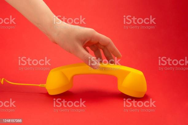 Yellow handset on a red background in woman hand picture id1248157055?b=1&k=6&m=1248157055&s=612x612&h=0ize4tcbrfz9c56n qxvzstxqwhnw4vonm2hro9c3 y=