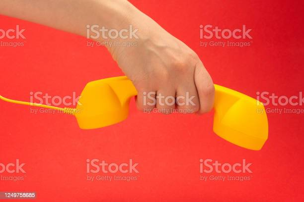 Yellow handset on a red background in woman hand picture id1249758685?b=1&k=6&m=1249758685&s=612x612&h=t 5h8wcp2c2ykclubiegj mi1w0diwygki5x6jexcjs=