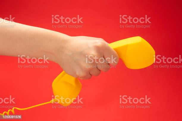 Yellow handset on a red background in woman hand picture id1253091526?b=1&k=6&m=1253091526&s=612x612&h=jcawejp6t 2cc1wzcjlzpmlu5lpwbw8icblsc0cz2xe=