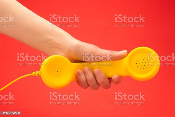 Yellow handset on a red background in woman hand picture id1253874568?b=1&k=6&m=1253874568&s=612x612&h=ygkveyj6jj2xzr2rnax bpni qotvm4pg9ww9gy2afs=