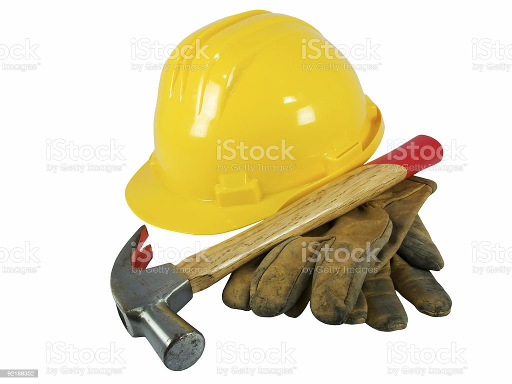 Yellow hardhat, old leather gloves and a hammer royalty-free stock photo