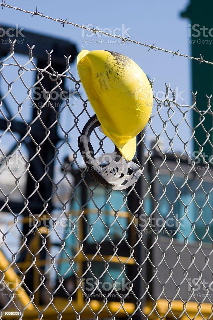 Yellow hardhat on fence royalty-free stock photo