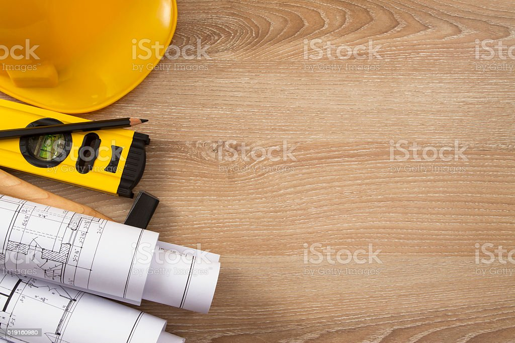 Yellow Hardhat Rolled White Blueprints on Wooden Board stock photo
