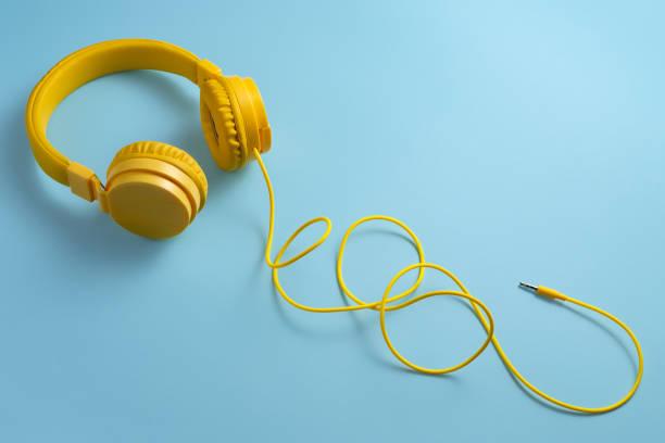 yellow headphones on blue background. music concept. - słuchawka nauszna zdjęcia i obrazy z banku zdjęć