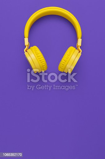 istock Yellow headphones on purple background. Music concept. 1065352170
