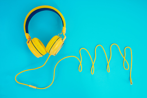 yellow headphones or earphone computer on a blue pastel background.