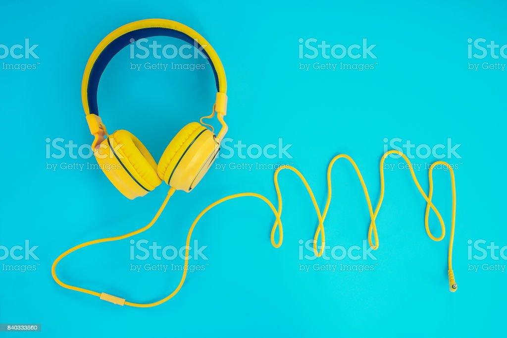 amarillo auriculares o equipo auricular sobre un fondo pastel azul - foto de stock