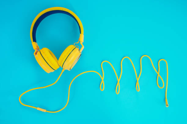 yellow headphones or earphone computer on a blue pastel background stock photo