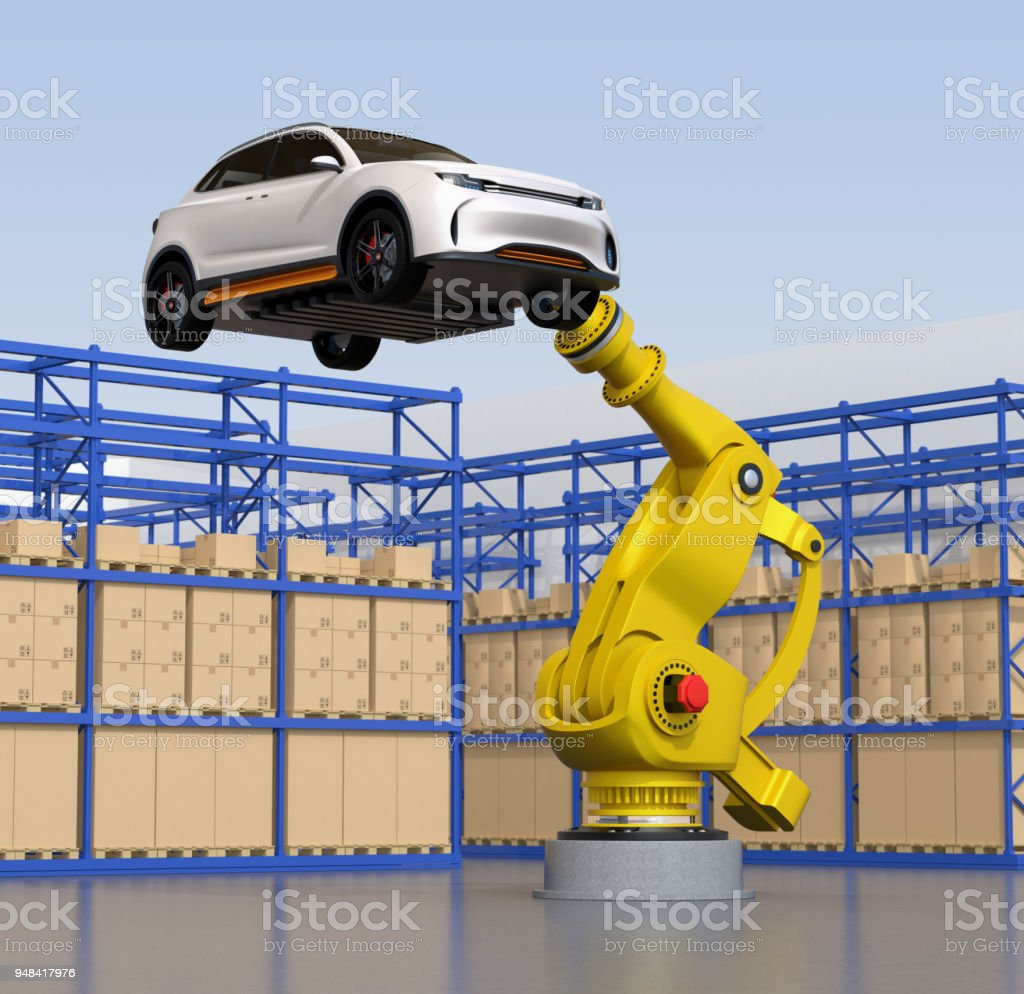 Yellow heavyweight robotic arm carrying white SUV in the assembly factory stock photo